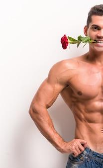 Muskulöser mann mit dem perfekten torso hält einzelne rose.