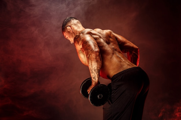 Muskulöser mann mit den dummköpfen, die übungen tun foto des starken mannes mit dem nackten torso lokalisiert auf weißer szene stärke und motivation hintere ansicht