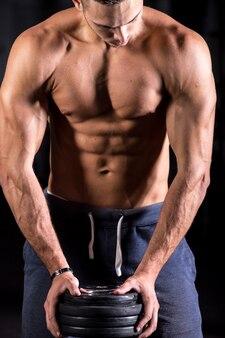 Muskulöser mann mit gewichten