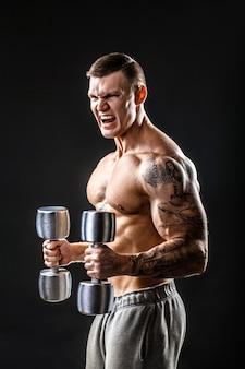 Muskulöser mann mit hantel. seitenansicht. schwarzer hintergrund