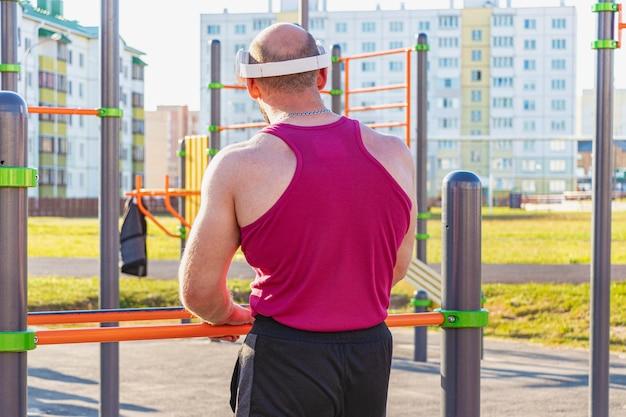 Muskulöser mann mit kopfhörern hört während eines sporttrainings musik auf dem spielplatz.
