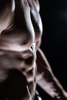 Muskulöser mann mit muskeln isoliert auf schwarzem hintergrund gesunder lebensstil
