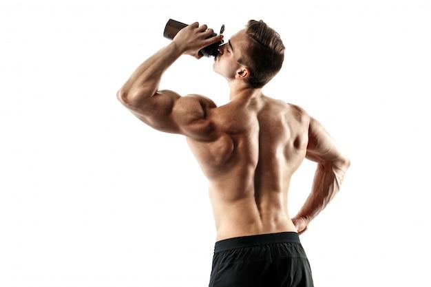 Muskulöser mann mit proteingetränk im schüttel-apparat über weißem hintergrund