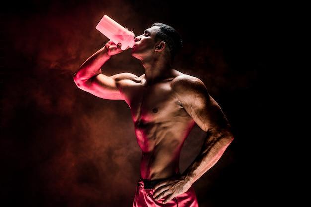 Muskulöser mann mit proteingetränk im schüttel-apparat