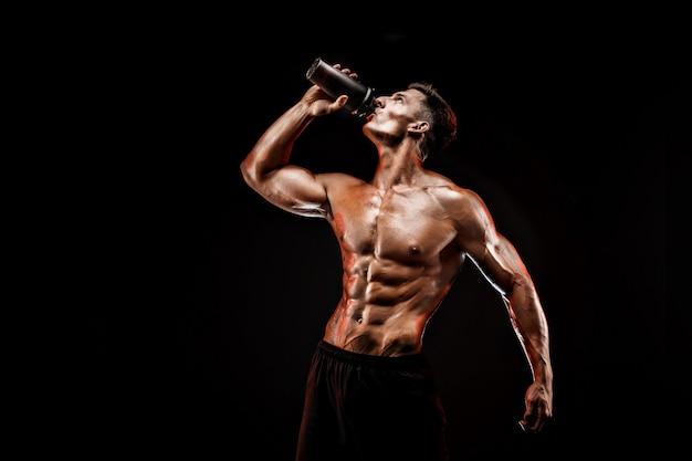 Muskulöser mann mit proteingetränk