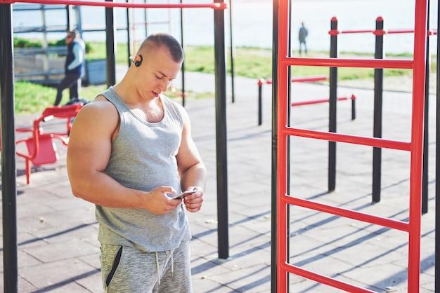 Muskulöser mann mit schönem torso, der auf horizontalen balken in einem park trainiert
