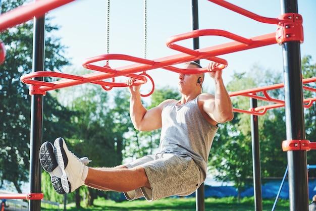 Muskulöser mann mit schönem torso, der auf horizontalen stäben trainiert