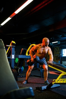 Muskulöser mann ohne hemd, der im rahmen seines bodybuilding-trainings hantelübungen macht. fitnessmotivation, sportlicher lebensstil, gesundheit, sportlicher körper, körper positiv