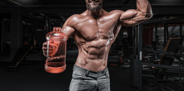 Muskulöser mann steht in der turnhalle mit einer riesigen flasche sportnahrung. fitness- und bodybuilding-konzept. gemischte medien