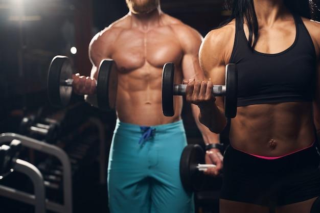 Muskulöser mann und athletische frau, die gewichte heben und im fitnessstudio trainieren