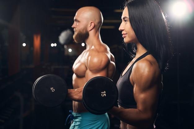 Muskulöser mann und starke frau heben hanteln beim training im fitnessstudio lifting