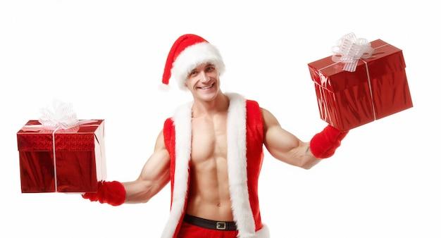 Muskulöser mann verkleidet als weihnachtsmann mit einem roten geschenk in jeder hand