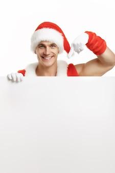 Muskulöser mann verkleidet als weihnachtsmann zeigt auf eine leere plakatwand, während lächelnd