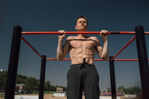 Muskulöser mann während seines trainings auf der straße mit reck. foto in hoher qualität