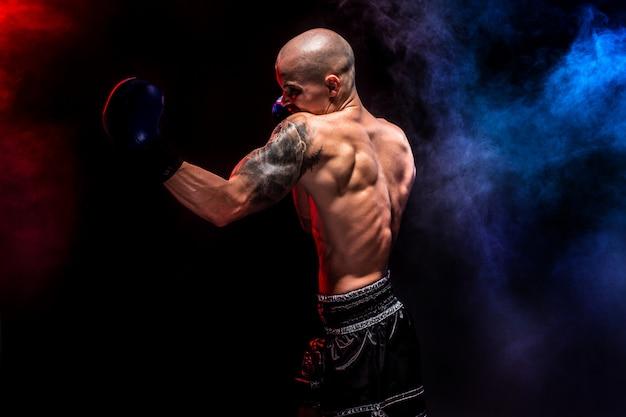 Muskulöser muay-siamesischer kämpfer, der im rauche locht