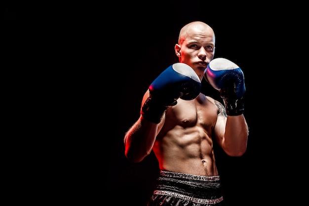 Muskulöser muay-siamesischer kämpfer, der in der dunkelheit locht