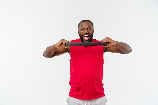 Muskulöser schwarzer junger mann, der mit gummibändern im studio, lokalisiert auf weiß trainiert.