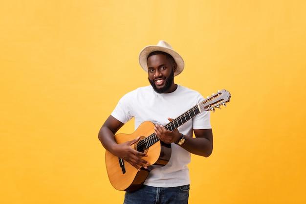 Muskulöser schwarzer mann, der gitarre spielt, jeans und weißes trägershirt trägt. isolieren sie über gelbem hintergrund.