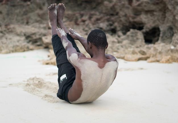 Muskulöser schwarzer mann, der training im tropischen strand hat
