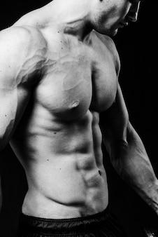 Muskulöser sexy torso des jungen sportlichen mannes mit perfekter bauchmuskelnahaufnahme. schwarz und weiß isoliert