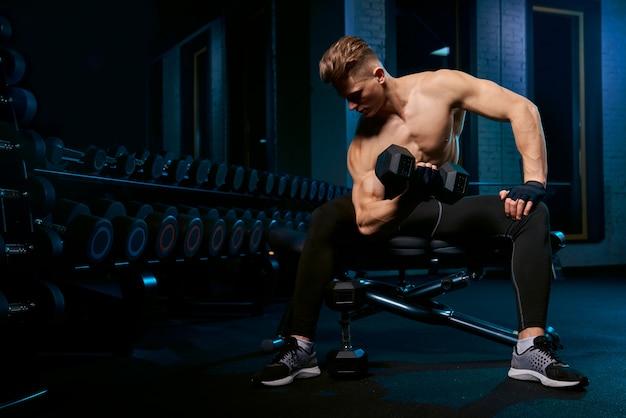 Muskulöser sportler, der bizeps mit hantel baut.