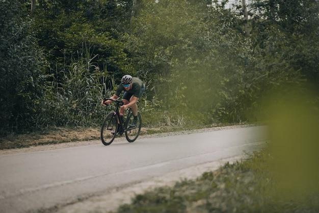 Muskulöser sportler, der fahrrad mit hoher geschwindigkeit zwischen wald reitet