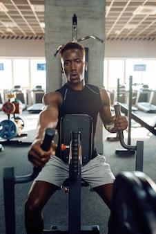 Muskulöser sportler in sportbekleidung am trainingsgerät beim training im fitnessstudio. training im sportverein, gesunder lebensstil