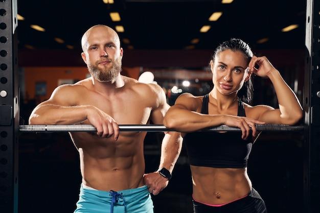 Muskulöser sportler und eine schöne frau, die im fitnessstudio auf einer langhantel steht und sich stützt