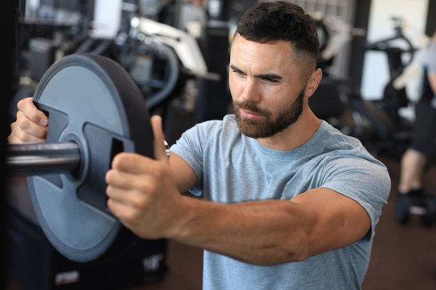 Muskulöser sportlicher indischer mann, der gewicht auf langhantel im fitnessstudio hinzufügt.