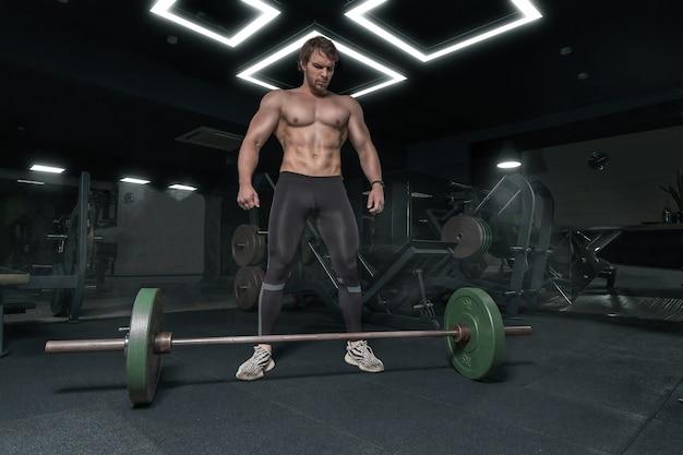 Muskulöser starker athletischer kerl ohne hemd, das die langhantel betrachtet