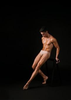Muskulöser tänzer, der auf barre sich lehnt