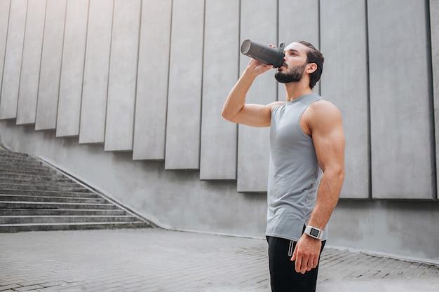 Muskulöser und gut gebauter junger mann steht und trinkt wasser aus schwarzer flasche