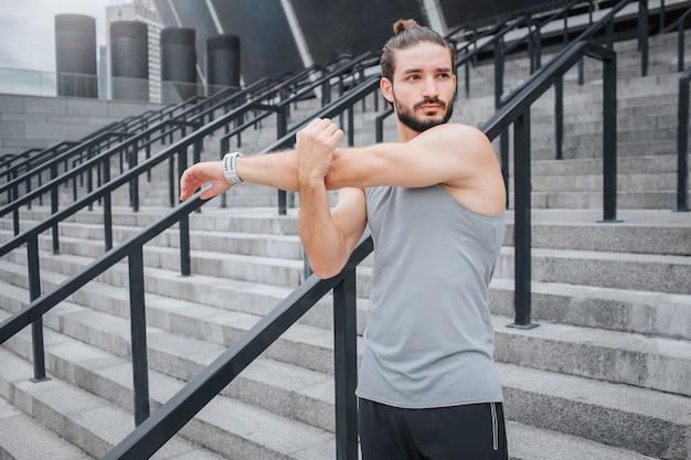 Muskulöser und starker junger sportler steht und streckt seine hände