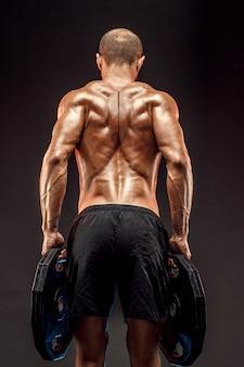 Muskulöses hemdloses männliches modell, das seine rückenmuskeln auf dunklem wandisolat zeigt.