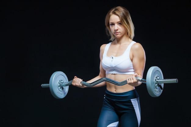 Muskulöses junges mädchen, das mit der lockigen langhantel an der turnhalle aufwirft