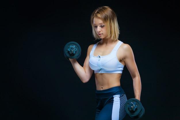 Muskulöses junges mädchen, das mit hanteln an der turnhalle aufwirft
