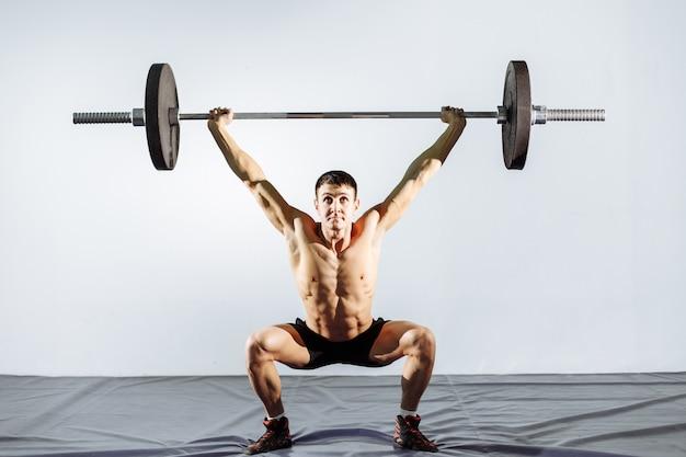 Muskulöses manntraining mit barbell an der turnhalle.
