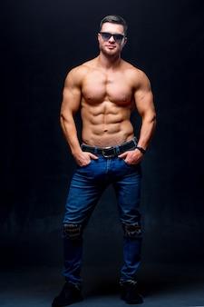 Muskulöses und fites junges männliches bodybuilder-fitnessmodell, das über dunkelheit aufwirft