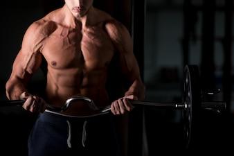 Muskulöser Mann, der eine Hantel im Fitnessstudio hebt