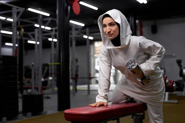 Muslim fit frau macht übungen mit hanteln, arabische frau konzentriert auf training, steht auf der seite und hält schweres gewicht in den händen