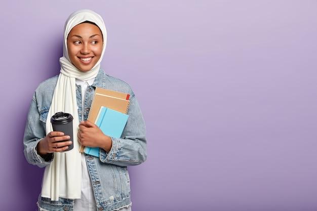 Muslim fröhliche frau mit dunkler haut, schaut weg, trägt weißen schleier, hält kaffee zum mitnehmen