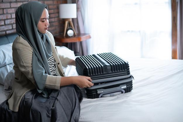 Muslim verschleierte frau, die einige kleider packt