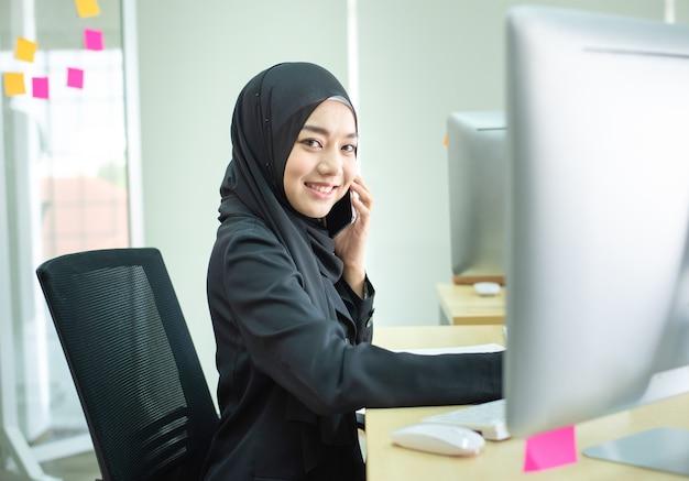 Muslimische arbeit der jungen frau im büro unter verwendung des telefons
