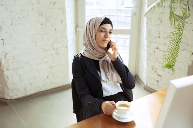 Muslimische arbeiterin telefoniert beim kaffeetrinken