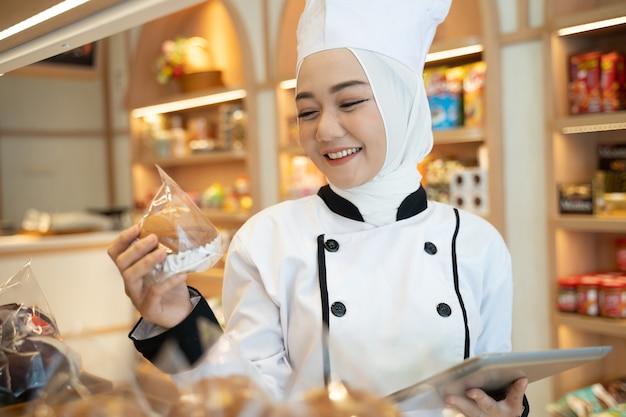 Muslimische asiatische bäckerin, die ihr produkt auf dem ausstellungsfach hält und tablettmenü betrachtet