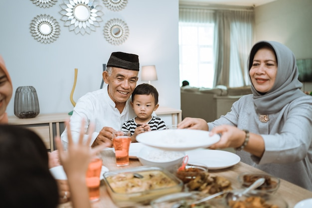 Muslimische asiatische familie und großeltern, die auf ramadan fasten. iftar abendessen pause