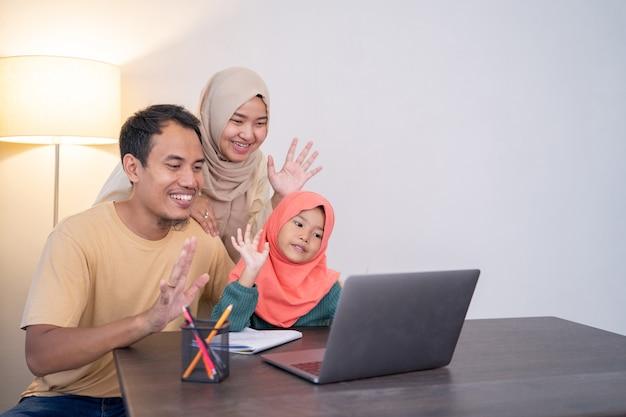 Muslimische asiatische familie winkt während videoanrufen mit tablet mit freund