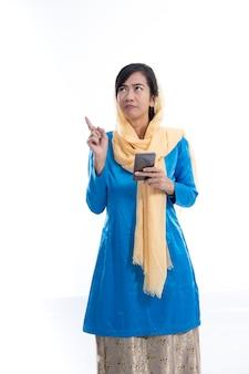 Muslimische asiatische frau denkt und hält handy, das nach oben schaut