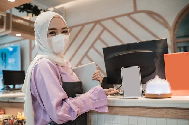 Muslimische asiatische frau, die mit pc arbeitet, während sie medizinische gesichtsmaske zum schutz im büro trägt