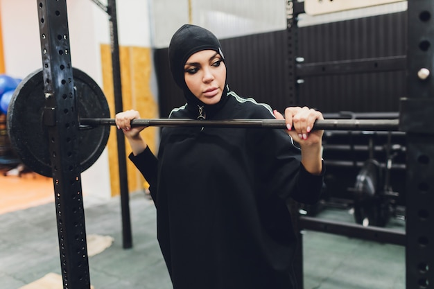 Muslimische asiatische frau im hijab, der in einem fitnessstudio trainiert.